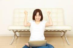 Mujer japonesa joven con el ordenador satisfecha Fotos de archivo