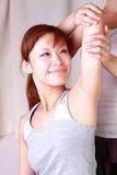 Mujer japonesa joven que consigue quiropráctica Imagenes de archivo