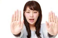 Mujer japonesa joven que hace gesto de la parada Fotos de archivo libres de regalías