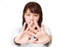 Mujer japonesa joven que hace gesto de la parada Fotografía de archivo