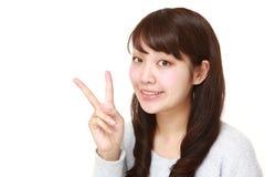 Mujer japonesa joven que muestra una muestra de la victoria Imágenes de archivo libres de regalías