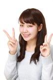 Mujer japonesa joven que muestra una muestra de la victoria Imagen de archivo libre de regalías