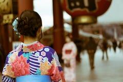 Mujer japonesa tradicional que lleva un kimono que mira la entrada del templo de Senso-Ji, Asakusa, Tokio, Japón Fotografía de archivo libre de regalías