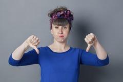 Mujer joven aburrida con los pulgares abajo que soplan hacia fuera sus mejillas Imagenes de archivo