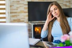 Mujer joven aburrida en la oficina que trabaja con un ordenador port?til y que mira fijamente la pantalla de ordenador imagenes de archivo