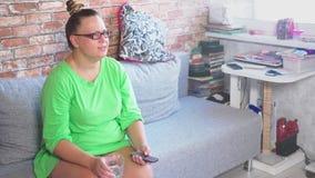 Mujer joven, aburrida que ve la TV el sentarse en el sofá en casa 4K metrajes