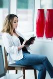 Mujer joven acertada con una tableta en interior moderno Fotografía de archivo
