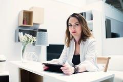 Mujer joven acertada con una tableta en interior moderno Imagen de archivo libre de regalías