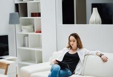 Mujer joven acertada con una tableta en interior moderno Imágenes de archivo libres de regalías