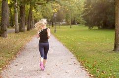 Mujer joven activa apta que activa a través de un parque Fotografía de archivo libre de regalías