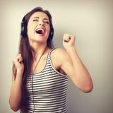 Mujer joven activa feliz de baile en auriculares que canta la canción Foto de archivo libre de regalías