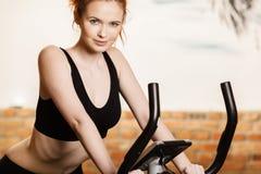 Mujer joven activa que hace ejercicio en la bicicleta en casa Imagen de archivo