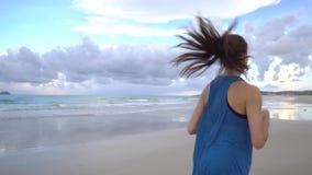 Mujer joven activa sana que corre a lo largo de línea de la orilla en la salida del sol El activar femenino almacen de metraje de vídeo