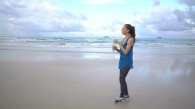 Mujer joven activa sana que corre a lo largo de línea de la orilla en la salida del sol El activar femenino metrajes