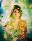 Mujer joven adorable con una guirnalda, en el parque Imágenes de archivo libres de regalías