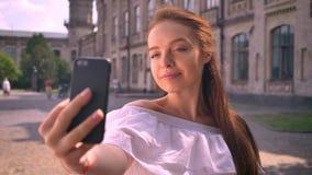 Mujer joven adorable del jengibre con los hombros desnudos que toman el selfie y que sonríen, tocando su pelo, colocándose en la  almacen de metraje de vídeo