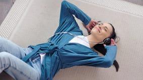 Mujer joven adorable feliz que disfruta de música que escucha usando los auriculares que mienten en alto ángulo de la alfombra metrajes