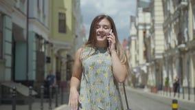Mujer joven adorable que habla por el teléfono celular que camina a través de la calle de la ciudad Muchacha de la diversión que  metrajes