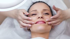 Mujer joven adorable sonriente del primer que disfruta de masaje de elevación facial en el salón del balneario de la belleza almacen de video