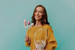 Mujer joven adulta adorable que lleva la ropa brillante el día de Pascua Cesta de la tenencia de la mujer con los huevos pintados imagenes de archivo