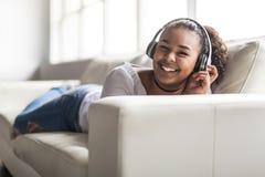 Mujer joven africana adolescente que se relaja en casa Imágenes de archivo libres de regalías
