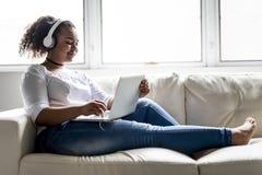 Mujer joven africana adolescente que se relaja en casa Fotos de archivo libres de regalías