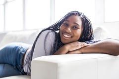 Mujer joven africana adolescente que se relaja en casa Foto de archivo libre de regalías