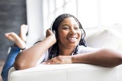 Mujer joven africana adolescente que se relaja en casa Fotografía de archivo