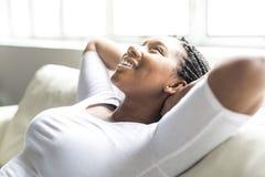 Mujer joven africana adolescente que se relaja en casa Imagenes de archivo