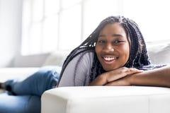 Mujer joven africana adolescente que se relaja en casa Fotos de archivo