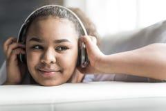 Mujer joven africana adolescente que se relaja en casa Imagen de archivo libre de regalías
