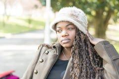 Mujer joven africana pensativa hermosa con el sombrero en el parque Foto de archivo libre de regalías