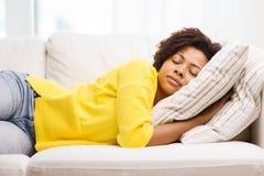 Mujer joven africana que duerme en el sofá en casa Imagen de archivo libre de regalías