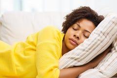 Mujer joven africana que duerme en el sofá en casa Foto de archivo libre de regalías