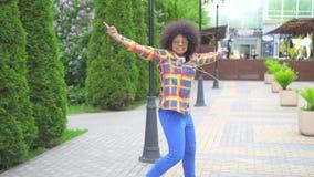 Mujer joven afroamericana alegre positiva que camina y que baila en la calle, contra el paisaje urbano almacen de video