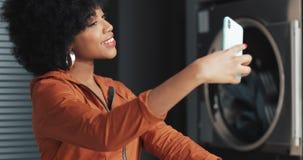 Mujer joven afroamericana atractiva feliz que hace un selfie en smartphone en la lavandería Lavadero p?blico del autoservicio almacen de metraje de vídeo