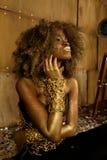 Mujer joven afroamericana elegante que se sienta en piso y que mira para arriba de tacto de su cara hermosa con maquillaje brilla Imagen de archivo