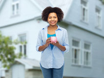Mujer joven afroamericana feliz con la hucha foto de archivo