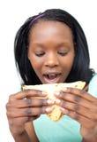 Mujer joven afroamericana que come un emparedado Imágenes de archivo libres de regalías