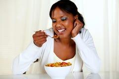Mujer joven afroamericana que come un tazón de fuente de cereales Foto de archivo