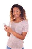 Mujer joven afroamericana que envía un mensaje de texto Imagen de archivo