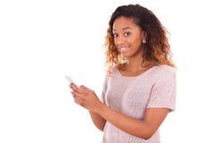 Mujer joven afroamericana que envía un mensaje de texto Imagen de archivo libre de regalías