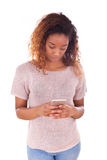Mujer joven afroamericana que envía un mensaje de texto Fotografía de archivo