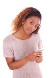Mujer joven afroamericana que envía un mensaje de texto Imágenes de archivo libres de regalías