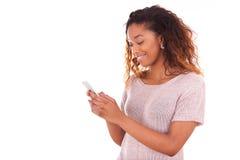 Mujer joven afroamericana que envía un mensaje de texto Foto de archivo