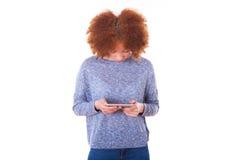 Mujer joven afroamericana que envía un mensaje de texto en ella elegante Fotografía de archivo libre de regalías