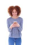 Mujer joven afroamericana que envía un mensaje de texto en ella elegante Fotografía de archivo