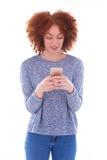 Mujer joven afroamericana que envía un mensaje de texto en ella elegante Imagen de archivo