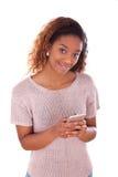 Mujer joven afroamericana que envía un mensaje de texto en su smartphone Imagenes de archivo