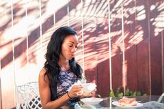 Mujer joven agraciada que sostiene una taza de café que se sienta afuera encendido Imagen de archivo libre de regalías